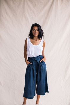 A sleek, yet comfortable style, our Navy Culottes are made from 100% linen and feature a pleated front, large pockets and a gathered waistband and tie. Designed to be worn at the waist, these elegant ¾ pants will complement any light top or summer shoe.
