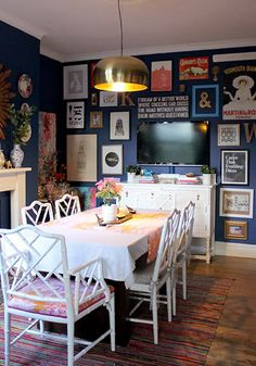 eclectic dining room with deep blue walls, bamboo chinoiserie chairs, a gallery wall, and a brass fixture