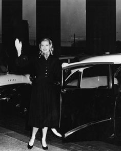 Grace Kelly waves as she steps into a taxi cab outside of Philadelphia's Thirtieth Street Station (August 2, 1955)