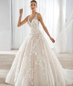 This classic ball gown features a V- neckline with a shimmering tulle skirt and romantic lace appliques. The sheer straps transition to an open V back and Chapel train.