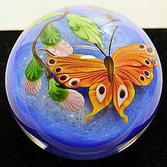 """GlassMaster Mayauel Ward's Butterfly paperweight. It features pink flowers, a colorful orange butterfly with a light blue background. It comes artist signed Mayauel Ward...PW21AORBUS and is approximately 2.80""""wide x 2.28""""high."""""""