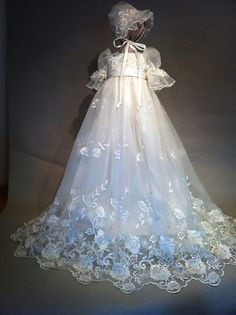 A romantic garden of roses are finely embroidered on the hem of this Victorian style gown. The flowers are accented with ivory pearls and the