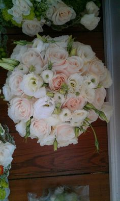 Creme roses, white lisianthus, and white ranunculus bouquet.  Designed by Flowers by Amanda