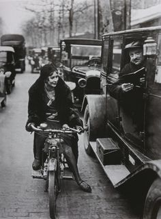 Unknown Photographer - Young Woman On A Motorcycle Asking A Parisian Chauffeur For Information, Paris, France 1930. Keystone-France/Gamma-Keystone/Getty images. . °