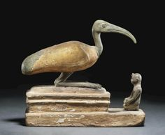 AN EGYPTIAN BRONZE AND WOOD IBIS COFFIN   THIRD INTERMEDIATE PERIOD, DYNASTY XXV, CIRCA 747-656 B.C.   The ibis depicted seated, the body sculpted in wood, covered in gesso and gilded, the legs, head and tail feathers each separately cast in bronze, the legs folded under, with a sinuous neck and long bill, the bronze figure of a Kushite pharaoh making an offering kneeling in front, wearing kilt and uraeus headdress, both mounted on a gesso painted wood coffin  7¼ in. (18.4 cm.) long