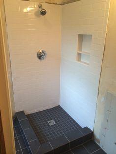 custom shower built using shower system black 8x10 tile installed on bathroom