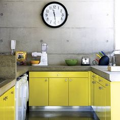 The cupboards are painted citrus yellow - the perfect contrast to the concrete walls and worktops.