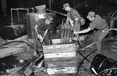 """Some moonshine drinkers say liquor made in a steam still has a superior taste.Here revenue agents are destroying the worm and flake stand in a steam outfit.When running the still, the moonshiners boiled water in the horizontal boiler (far left), forcing steam through two pipes into the mash-filled """"pot"""" (center left)."""