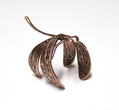 This adorable little copper plated dragonfly's wing wraps comfortably around your finger for day and evening wear. It snuggles on your finger and follows you everywhere. ADORABLE!    This Dragonfly is made from copper plated brass stamping, and is very detailed. The ring bass is adjustable to fit onto a 5-8 ring size comfortably. Length is 1 1/2 inches (38mm) long by 7/8 (20mm) inch wide.