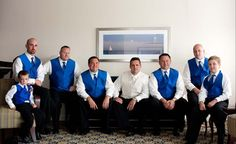 groomsmen wearing white shirt with black pants royal blue vest green tie green corsage and green shoes :)