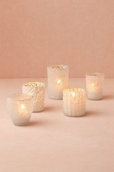 assorted white frosted candle votives scattered throughout the tables, buffet, dessert table and bars
