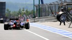 A loose wheel rolls away from the car of Mark Webber during the 2013 German Grand Prix