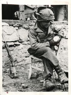 1944- U.S. 83rd Division soldier examines an alarm clock he found in town of Gey, Germany.