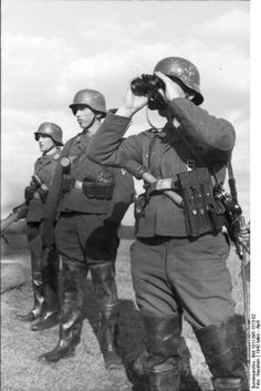 Three soldiers of the Luftwaffe Field Division on patrol (?) pose to scan the horizon. Note the stick grenades. All three wear the German version of the Wellington boot, which most likely suggests they were operating in marshlands, or other waterlogged terrain. The Field Division was Goering's contribution to the line infantry although it was initially created to provide security to forward military airfields.