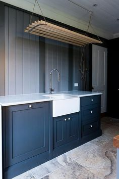 Gorgeous blue laundry room boasts blue cabinets adorning square polished nickel knobs and a white marble countertop fitted with a farmhouse sink with nickel gooseneck faucet positioned in front of a light blue beadboard wall beneath a wood and rope pull down drying rack fixed to a white shiplap ceiling.