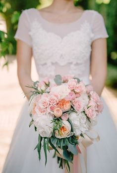 A romantic bouquet of peonies, roses, ranunculus, and eucalyptus was the perfect arrangement of complement this bride's lace and tulle ball gown wedding dress. Lauren's Floral Art, a florist based in Lawrenceville, Georgia, whipped up this lovely look.