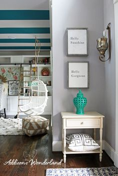 A small foyer accent wall gets a sophisticated touch with a side table, pillows, sconces and vase from HomeGoods. Sponsored by HomeGoods.