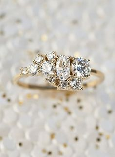 A custom cluster ring comprised entirely of heirloom diamonds of various cuts and sizes. Shown in 14kt yellow gold with a high polish finish.
