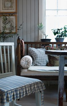 A swedish pine sofa is nicely complemented with a mix of creamy whites and blues on the walls and in the fabrics.
