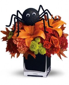 spooky sweet bouquet a big black spider creeps your way to wish you a happy halloween this fun halloween floral decoration presents lush orange and green