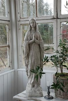 Antique marble statue of The Virgin Mary used in a sunroom . . .