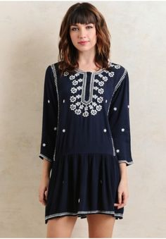 Easy-to-wear and darling, this navy drop-waist dress features intricate floral embroidery and button closures partially down the front.