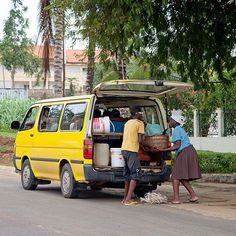Bus conductor helps a woman load her goods in the booth. Sao Tome. ©Andreu Trias