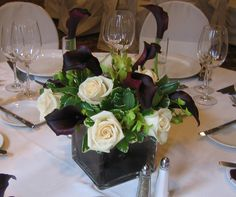 This is a cube vase floral arrangement that features white roses, eggplant miniature calla lilies and green dendrobium orchids. See our entire selection at www.starflor.com.  To purchase any of our floral selections, as gifts or décor, please call us at 800.520.8999 or visit our e-commerce portal at www.Starbrightnyc.com. This composition of flowers is generally available for same day delivery in New York City (NYC).  SQ229