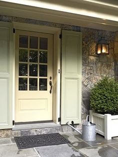 Stone home, exterior door with large glass panes and shutters flanking door.