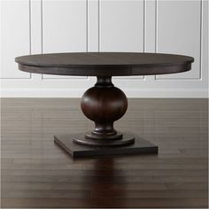 """Shop Winnetka 60"""" Round Dark Mahogany Extendable Dining Table. Designer Blake Tovin's richly appointed round table showcases a dramatic turned pedestal base and gracious tabletop with classic recessed apron containing open grain and knots that make each solid wood dining table unique."""