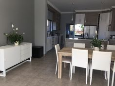 Open plan dining, kitchen area in natural tones. Grey tiles, wood effect with satin white. My house is complete!