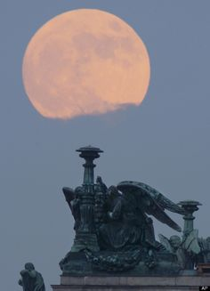"""The full moon rises in the clouds behind statues of angels fixed at the St. Isaak's Cathedral in St.Petersburg, Russia, Saturday, May 5, 2012. Saturday's event is a """"supermoon,"""" the closest and therefore the biggest and brightest full moon of the year. (AP Photo/Dmitry Lovetsky)"""