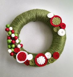 This 10 inch wreath is wrapped with a cozy camel two-toned green yarn. All flowers are hand cut and made with a sturdy wool felt blend. Its the