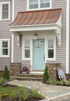 Light teal front door. Cute wood awning over door. Great idea for plain jane front of house.