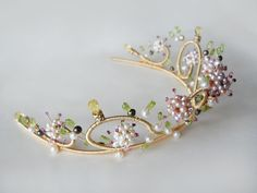 This stunning tiara captures the beauty of nature with this intricately beaded sculptural work. It showcases the white to mauve color-graduated pearl clusters incrusted with tiny rubies twinkling in between a delicate pale green peridot leaves setting. Beautifully handcrafted and accented with golden citrine briolettes and crystals and white and bronze color freshwater pearls. This tiara comes with three small hair combs attached for secure positioning in your hair. It measures 2 high in the…