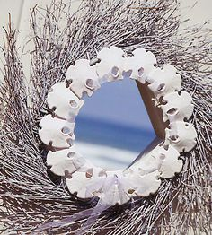 Sand Dollar Wreath  --  Whether your door is a gateway to the beach or leads right into a drift of snow, dress it with a wreath adorned with coastal elements. Spray-paint a grapevine twig white, then hot-glue a circle of sand dollars or other flat shells around the wreath opening. Weave a sheer organdy ribbon through the shells and tie the tails into a simple bow.