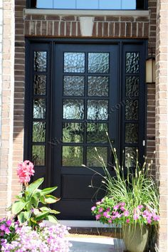 This Beautiful Black Front Door is better then a Fiberglass door. It is a charming classic French Style Door with a twist. This is a Wood Door set up as a Single Exterior Door with Two Side Lites. Instead of a typical clear glass door, they installed non-clear glass in the door. Perfect Door for a Brick House. Door was Purchased at www.nicksbuilding.com