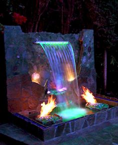 Outdoor fire pit ideas using fire glass. Modern outdooor fireplace designs using burning glass. - waterfall with colored lights and fire Ray needs to build this - Backyard Water Feature, Ponds Backyard, Fire Pit Backyard, Backyard Landscaping, Rustic Backyard, Fire Pit With Water Feature, Landscaping Ideas, Garden Ponds, Koi Ponds