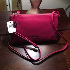 NWT! Coach magenta Crossbody! New with tags! Just in! Brand new Crossbody bag in Cyclamen Pink leather. Featuring two zippered pockets with interior pockets on each side. Locking top zipper tab and adjustable strap. Silver hardware. Coach Bags Crossbody Bags