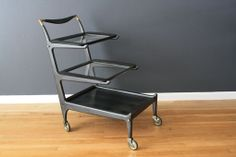 This is a Mid-Century Italian black ebonized bar/tea cart by Cesare Lacca as seen in Madmen. It has three removable shelves and beautiful, sculptural details.