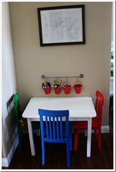 I love the idea of using a bathroom towel rack to hold the buckets of art supplies.  cute!