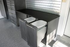 """Custom Garage cabinets with 8"""" bar pulls in our newest color of Silver Vien . Also a custom designed Shoe center with bi-fold doors to either side to be used for golf club storage. Trash / Recycle center built into workbench system with a 9 drawer tool storage chest and custom epoxy floor finish"""