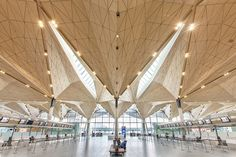 A faceted ceiling comprising dozens of gold-hued metal panels soars over the public spaces in a new terminal for Pulkovo International Airport in St. Petersburg, Russia, created by a team that included the U.K.'s Grimshaw Architects (as concept architect), the Danish engineering and architecture firm Ramboll (as lead design consultants), and the London design firm Pascall+Watson (as executive architects).