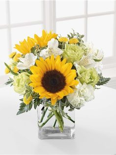 Yellow and white flowers including sunflowers in a clear block vase FTD C11-4152