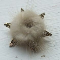 Fur star vintage brooch. Circa 1960s real vintage retro jewellery. Cream coloured fur onto a star shaped brooch in gold metal.