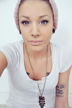 Beautiful girl with blue eyes, septum piercing, medusa, diamond tattoos, and owl necklace.