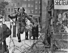 An East Berlin border guard leaps across the barbed wire into West Berlin - and freedom. Work on the permanent concrete wall had just begun. After this escape, officers kept guards well behind the wire barriers to thwart any other attempts, 1961.