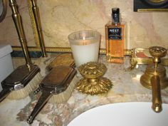 In NY powder room of Howard Slatkin, custom designed sink hardware made by Guerin, New York.  Scented candle & liquid soap by Nest Fragrances,