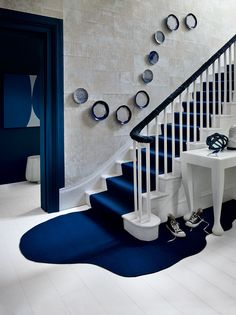 The marine tones of a bespoke stair runner cascade down to form a serene pool on the floor in this gorgeous home. #staircase #stairs #interiordesign