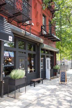 Brunswick Café in Brooklyn. Charcoal black exterior, window façade with lights in door.